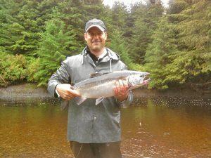 Lodge guest lands a bright Silver Salmon while fly fishing