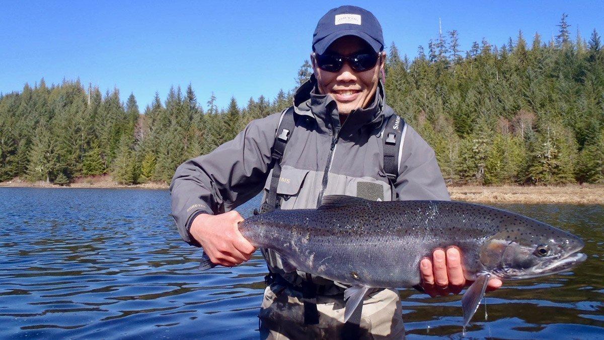 Head fishing guide Jay Mar lands beautiful Steelhead trout in sunny southeast Alaska
